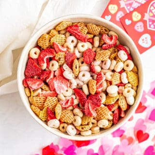A large bowl full of toddler Valentine's Day snack mix with cereal, yogurt covered raisins and dried strawberries