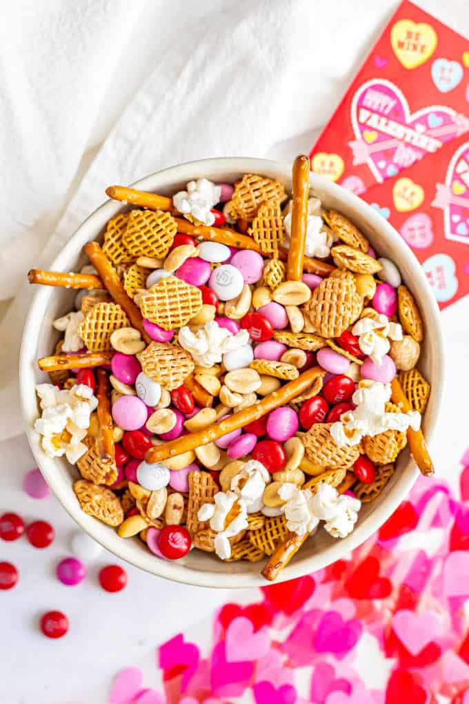 Chex mix snack with cereal, pretzels, popcorn, peanuts and Valentine's M&Ms in a bowl