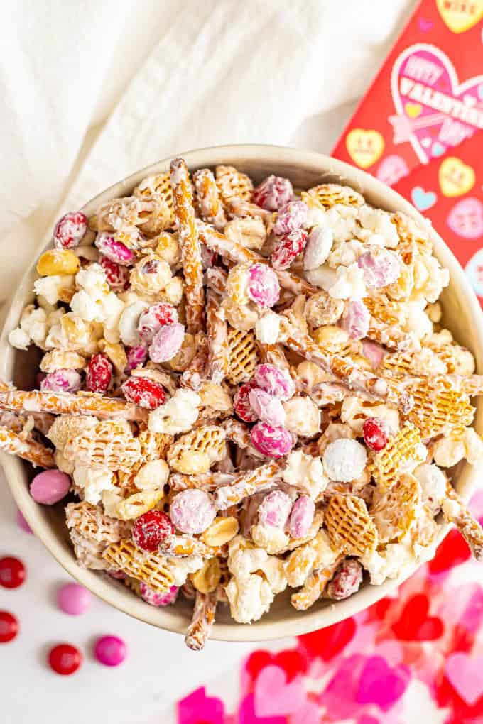 A white chocolate coated Valentine's Day snack mix served in a large bowl with Valentine's decorations nearby