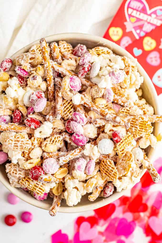 A white chocolate coated Valentine's Day snack mix served in a large bowl