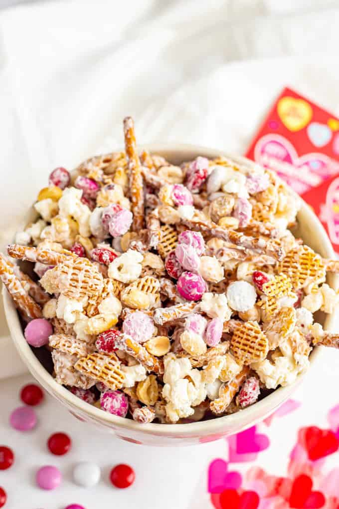 A Valentine's Chex mix with cereal, pretzels, popcorn and red, pink and white M&Ms