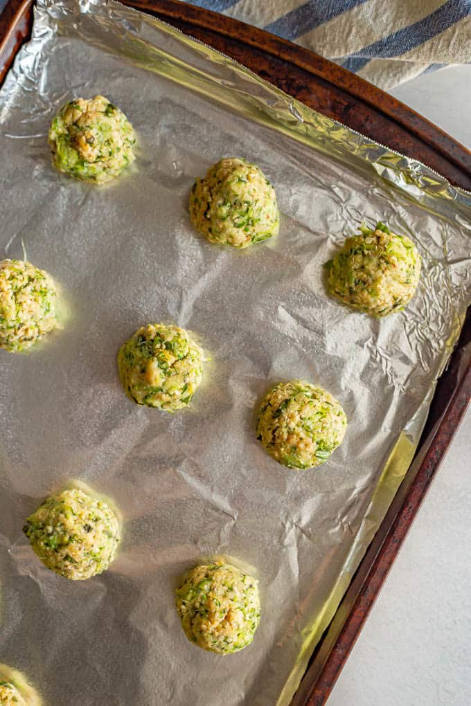 Rolled zucchini meatballs on a sheet pan before being baked