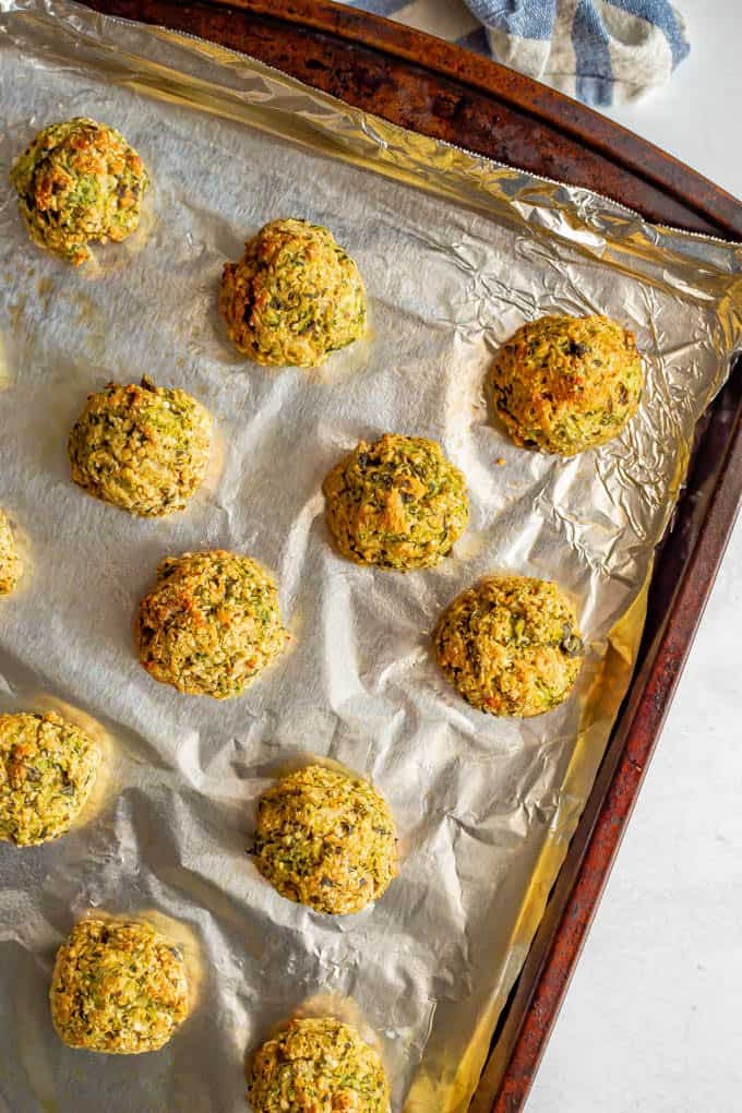 Baked zucchini meatballs on a foil-lined sheet pan