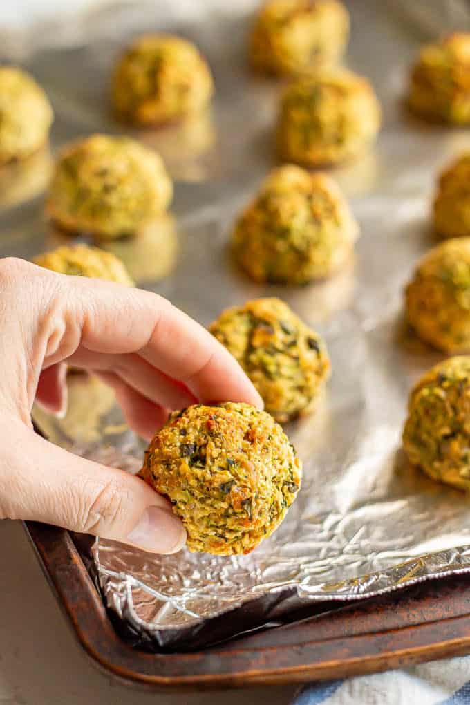 A hand picking up a baked veggie meatball from a sheet pan