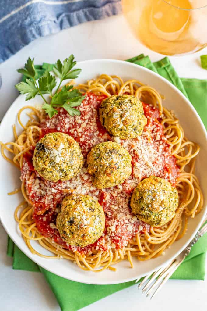 Vegetarian meatballs on top of a bed of spaghetti noodles with marinara sauce in a white bowl