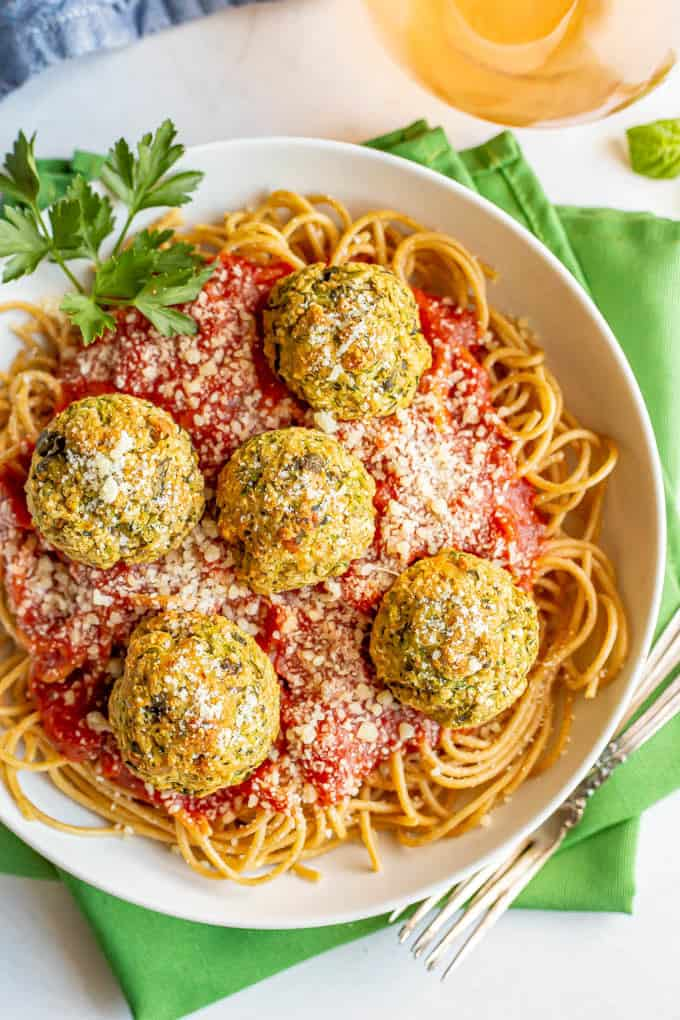 Baked vegetarian meatballs on top of spaghetti noodles with marinara sauce in a white bowl