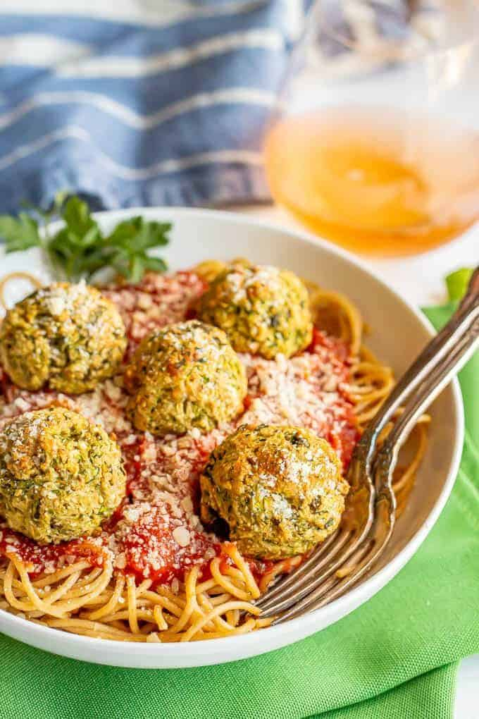 Baked zucchini meatballs on top of spaghetti noodles with marinara sauce in a white bowl