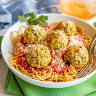 A bowl of spaghetti topped with marinara sauce and vegetarian meatballs with two forks resting in the bowl