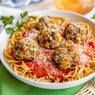 Veggie meatballs served with spaghetti and sauce in a large white bowl