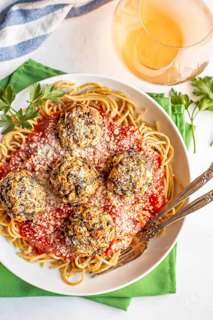Mushroom meatballs served over spaghetti noodles and marinara in a white bowl with forks tucked in