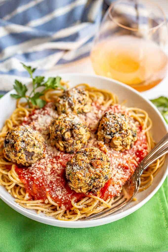Vegetarian mushroom meatballs served over spaghetti noodles and marinara in a white bowl with forks tucked in