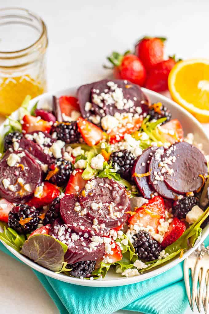 A salad bowl with mixed greens, beets, fresh berries sand feta cheese and a citrus dressing on top