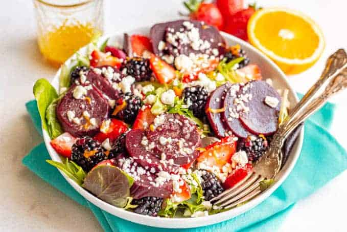 A salad bowl with mixed greens, beets, fresh berries sand feta cheese