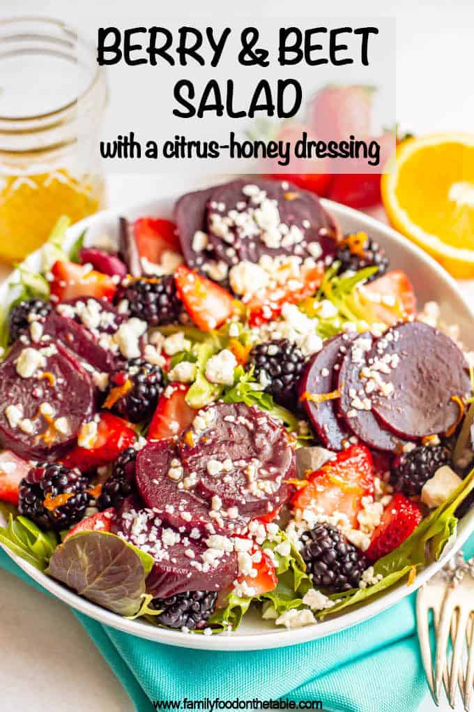 A salad bowl with mixed greens, beets, fresh berries sand feta cheese and a text box at the top