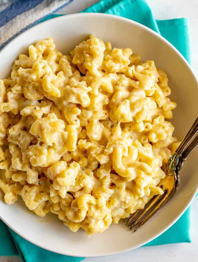 Creamy crock pot mac and cheese in a large serving bowl with two forks alongside
