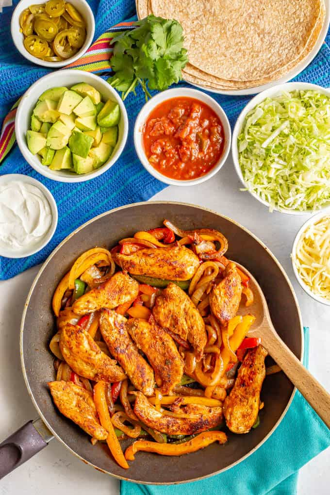 A skillet of fajita chicken and peppers surrounded by bowls of toppings and a plate of flour tortillas