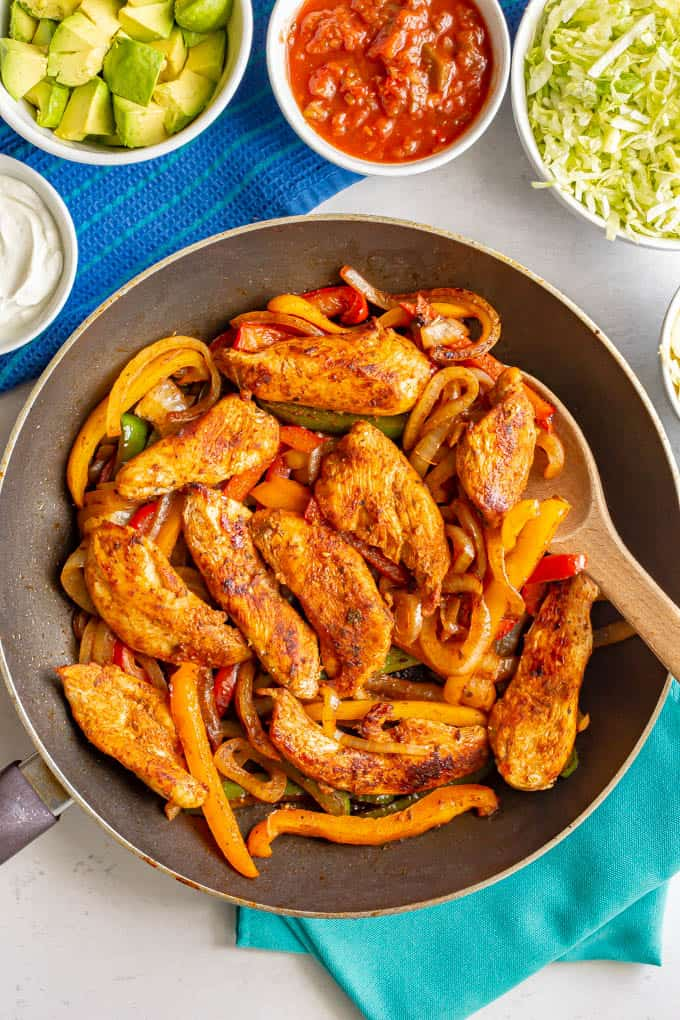 A skillet of cooked chicken fajitas with bell peppers and onions and bowls of toppings nearby