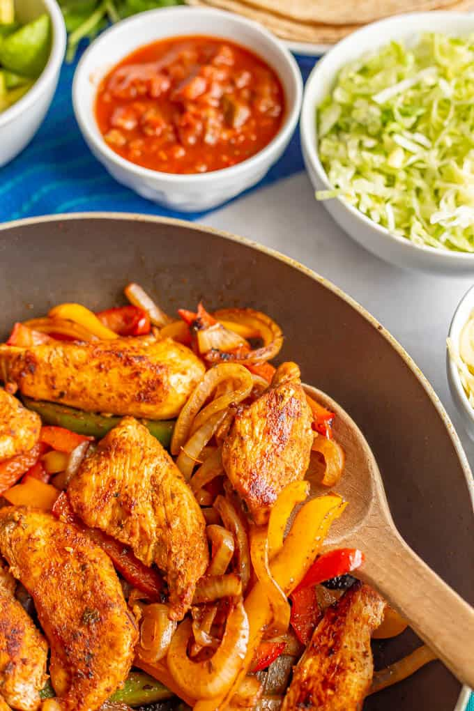 A wooden spoon scooping up some fajita chicken and peppers from a skillet, with bowls of toppings in the background