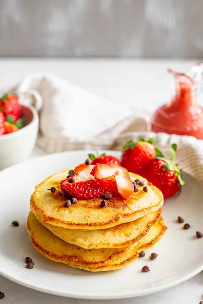 A stack of fluffy pancakes with strawberries and mini chocolate chips