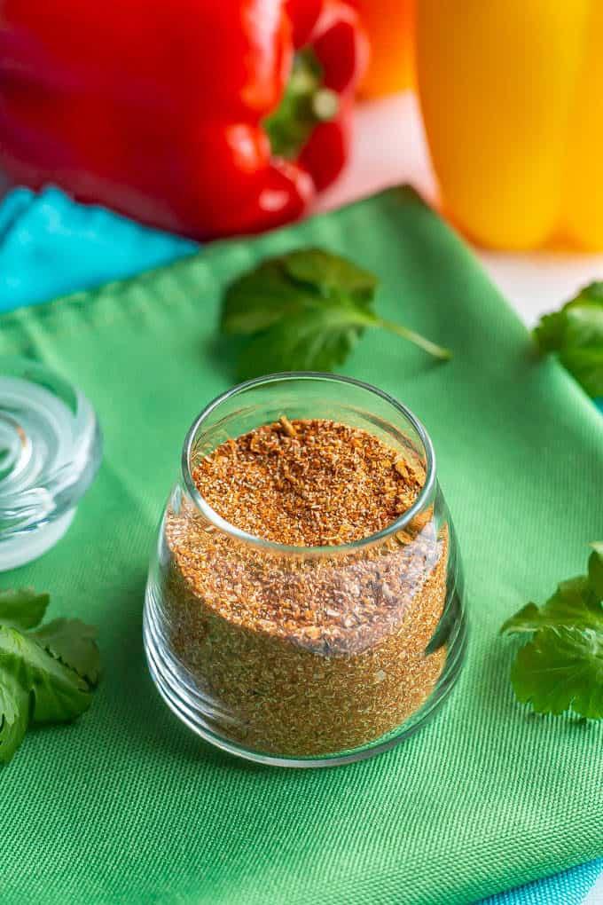 A small glass jar full of a seasoning mix set on a green napkin
