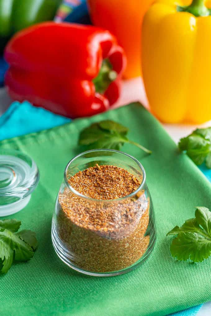 Fajita seasoning in a small glass jar on a green napkin with peppers and cilantro nearby