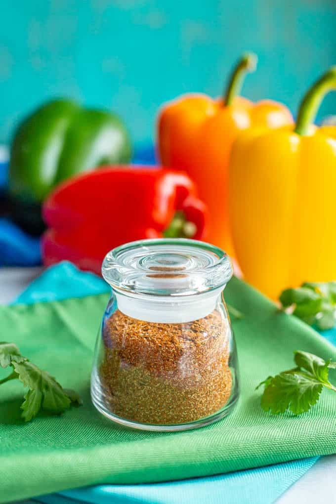 Fajita seasoning in a small glass jar with a lid on, set on a green napkin with peppers and cilantro nearby