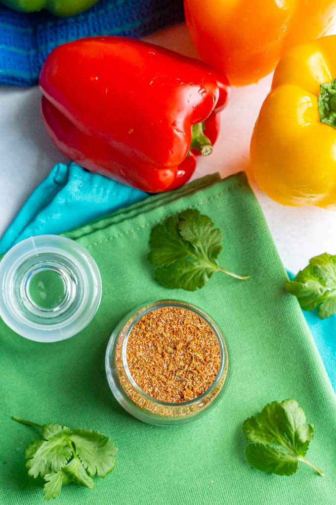 Overhead photo of a glass jar of seasoning mixture with sprigs of cilantro and bell peppers nearby
