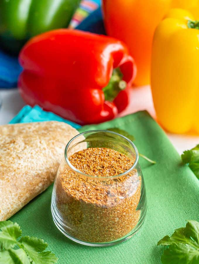 Homemade fajita seasoning in a small glass jar with flour tortillas, bell peppers and cilantro sprigs nearby