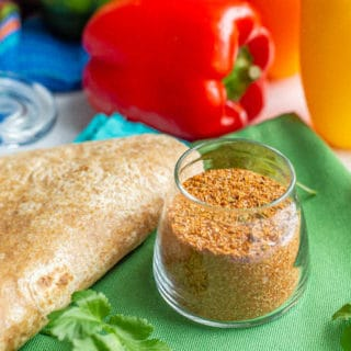 Fajita spices in a small glass jar with flour tortillas, bell peppers and cilantro sprigs nearby