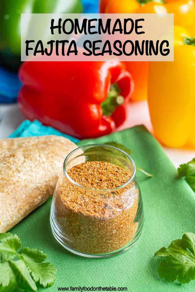 Homemade fajita seasoning in a small glass jar with flour tortillas, bell peppers and cilantro sprigs nearby and a text box at top