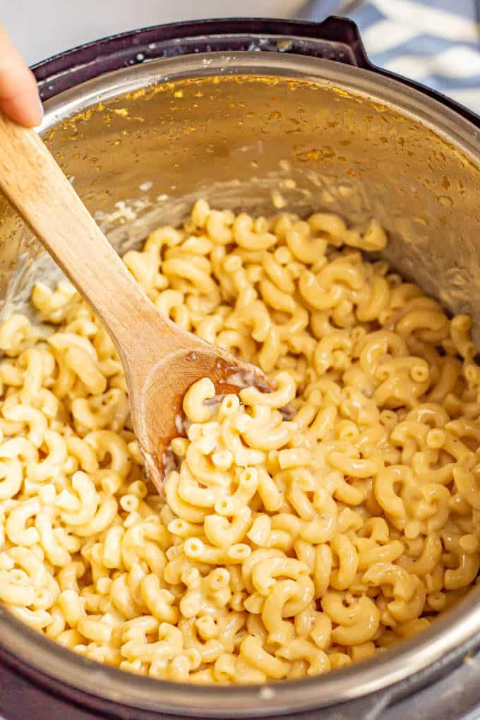 A wooden spoon stirring creamy macaroni and cheese in an Instant Pot insert