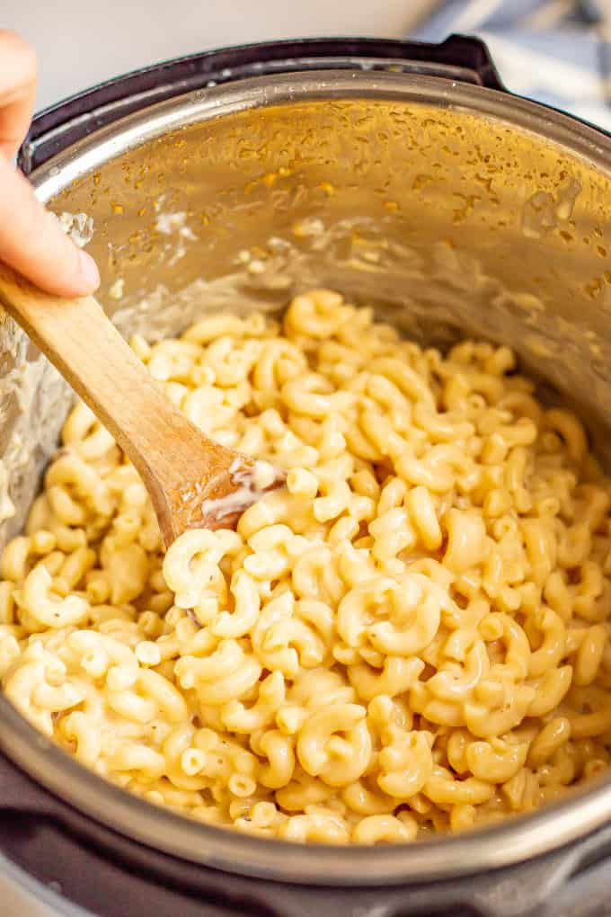 A wooden spoon stirring mac and cheese in an Instant Pot insert