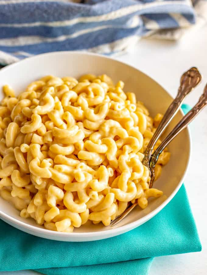 Creamy macaroni and cheese served in a bowl with two forks tucked in