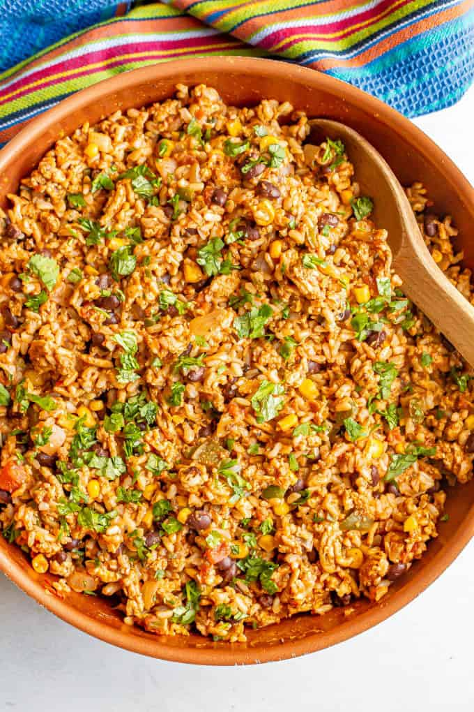 A ground turkey, rice and black bean mixture in a large skillet with cilantro sprinkled on top