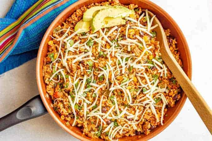 A Mexican turkey and rice skillet with cilantro, cheese and avocado on top