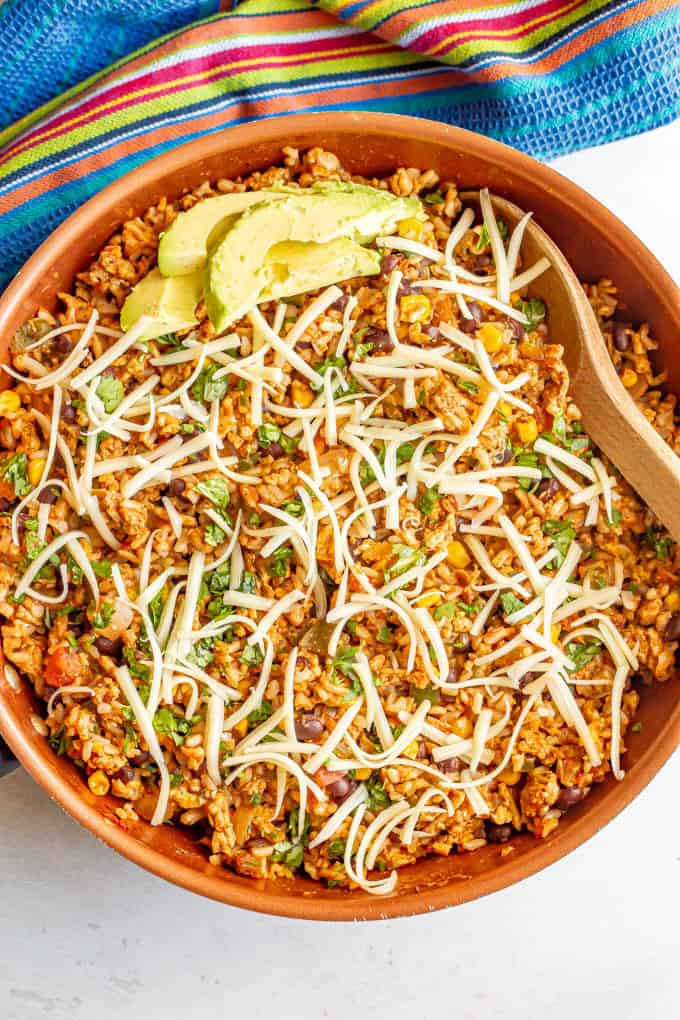 A Mexican ground turkey and rice skillet with cilantro, cheese and avocado on top