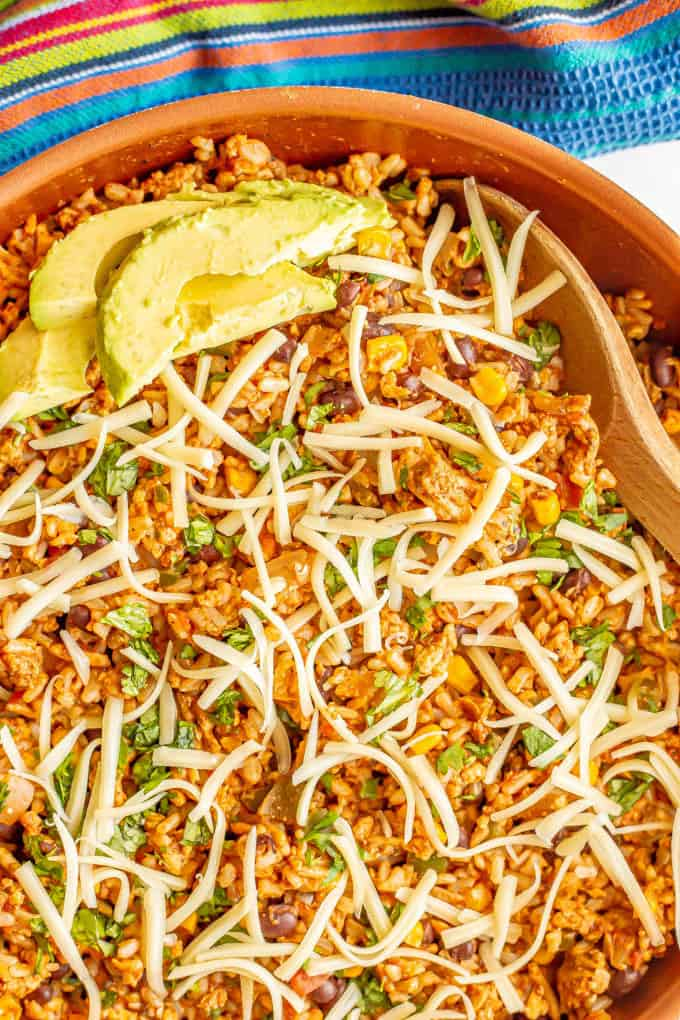 Close up of a Mexican turkey and rice skillet with cilantro, cheese and avocado on top and a wooden spoon resting in the pan