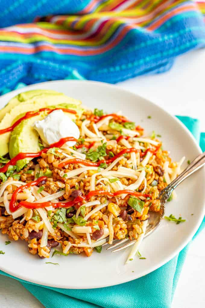 A plate full of Mexican fried rice with toppings and a fork alongside