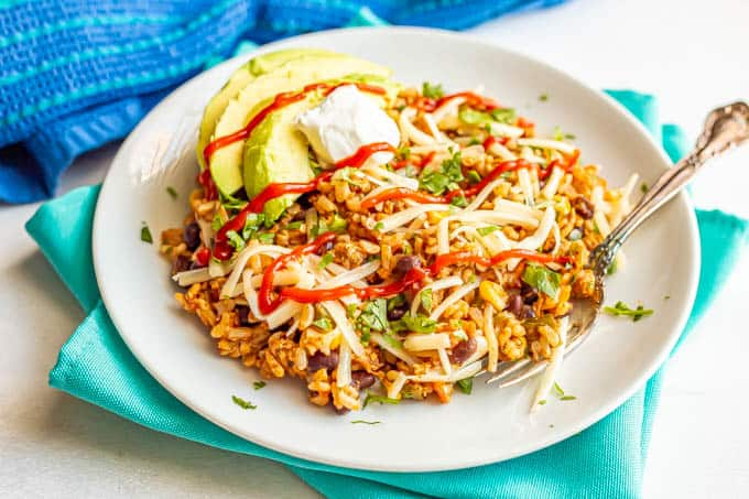 Mexican fried rice served on a white plate with a fork and topped with cilantro, shredded cheese, avocado and sriracha sauce