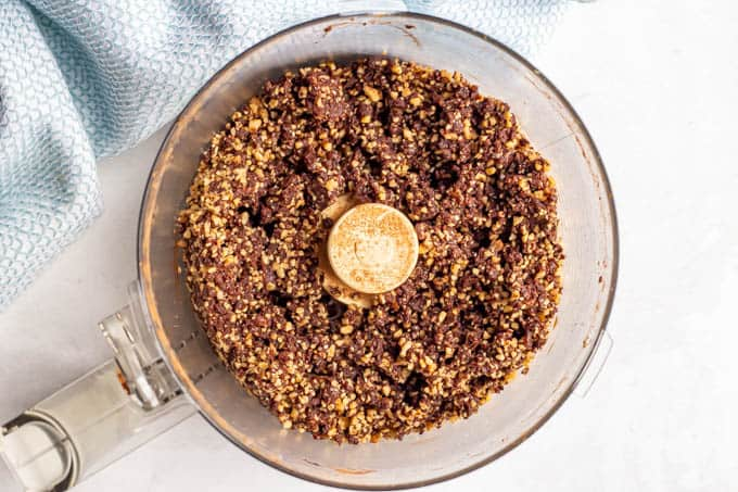 A raw date and walnut and cocoa mix broken down into crumbles in a food processor