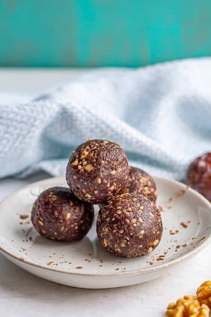 A stack of raw date brownie balls on a plate with a sprinkling of cocoa powder