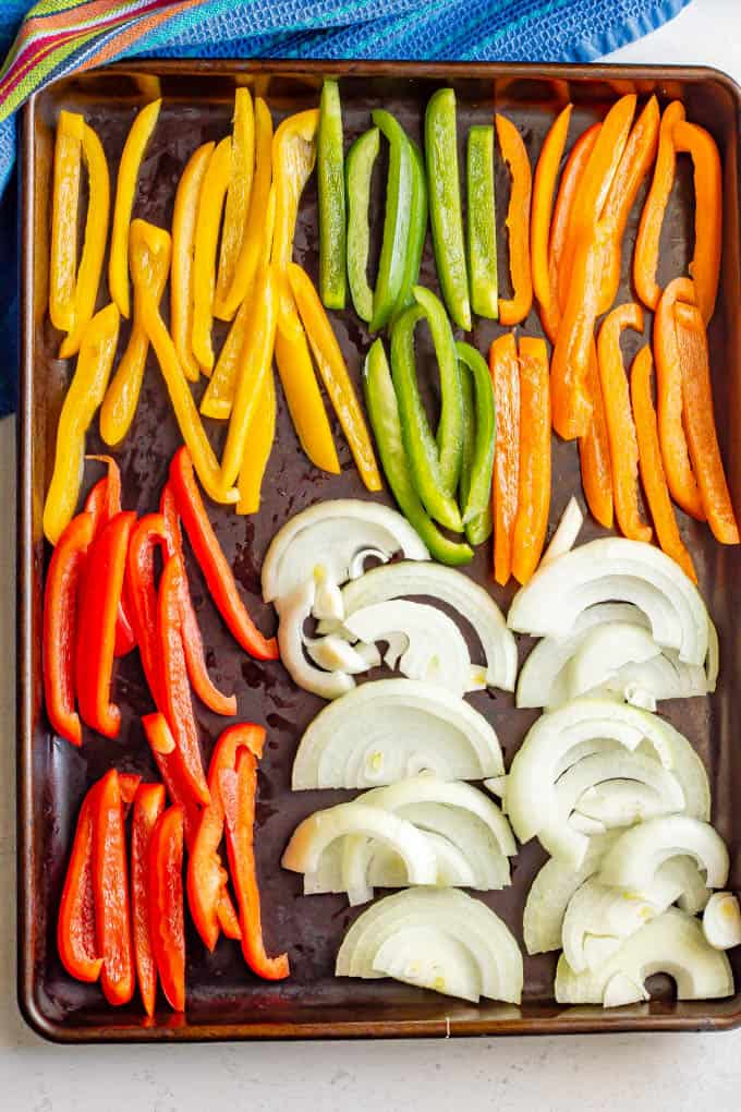 A sheet pan with strips of red, yellow, green and orange bell peppers and sliced onion before roasting