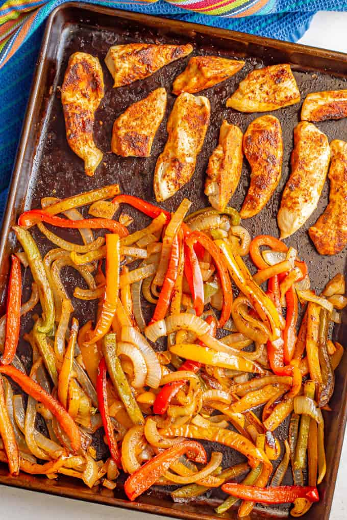 A sheet pan with seasoned chicken and mixed peppers and onions after roasting