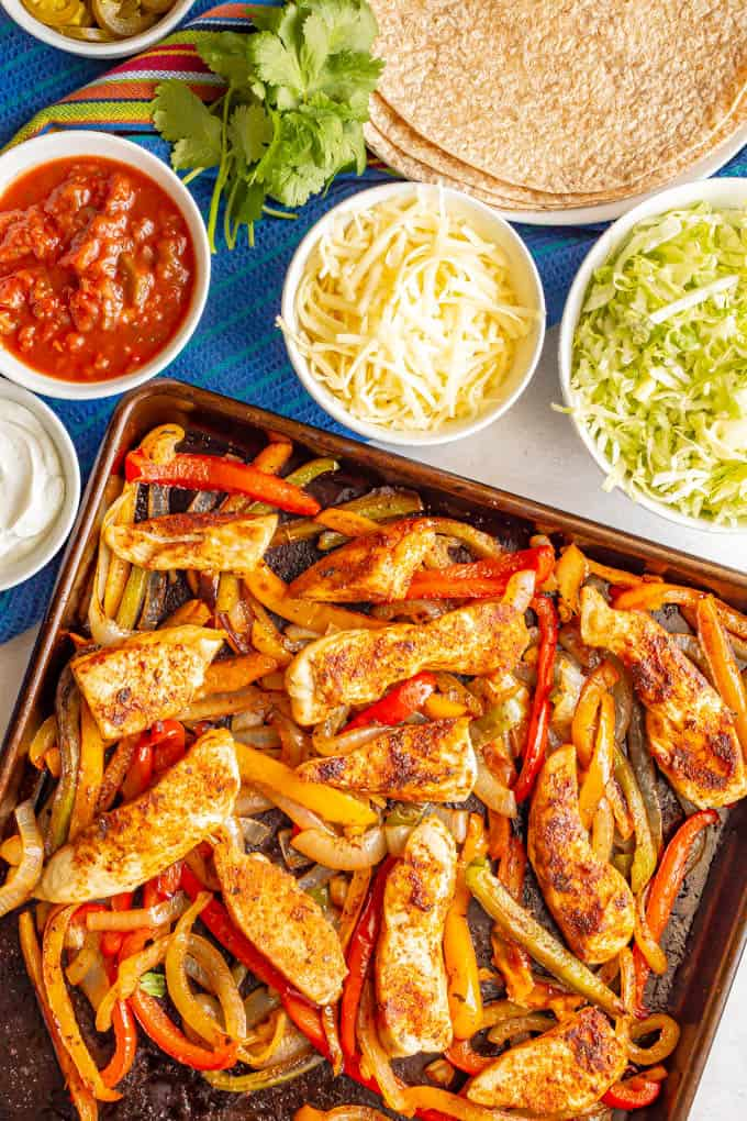 Baked chicken fajitas with bell peppers and onions and nearby bowls of toppings and a plate of tortillas