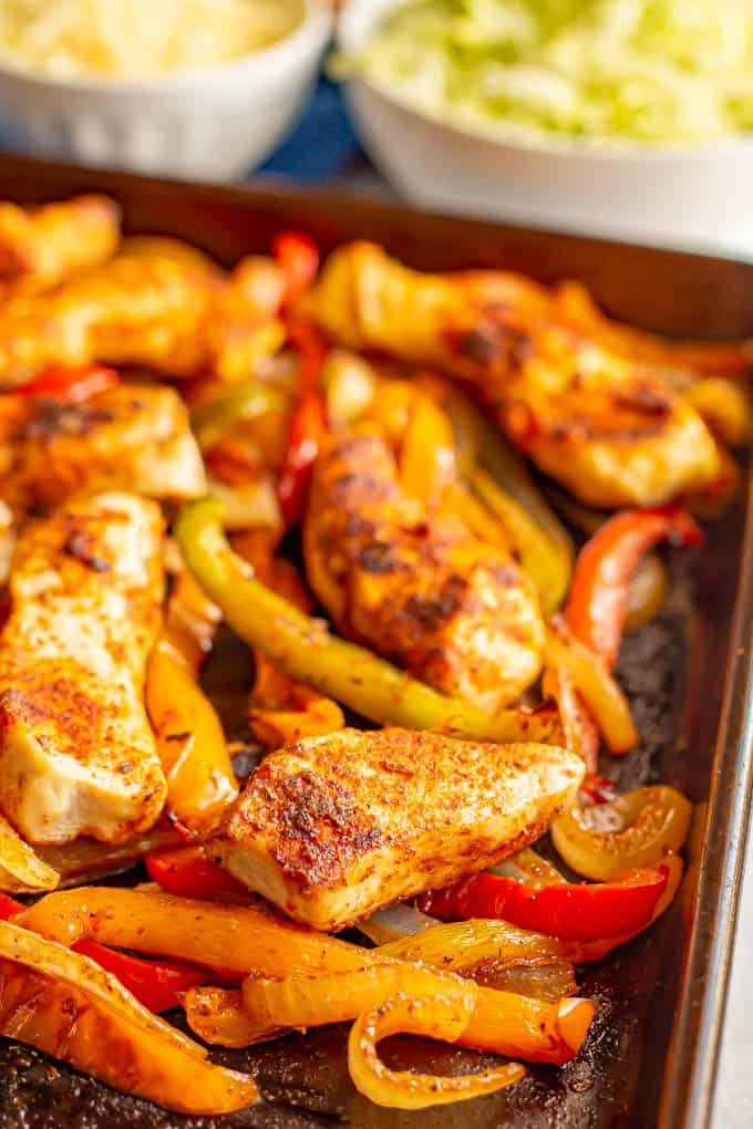 Close up of roasted chicken and bell peppers on a baking tray
