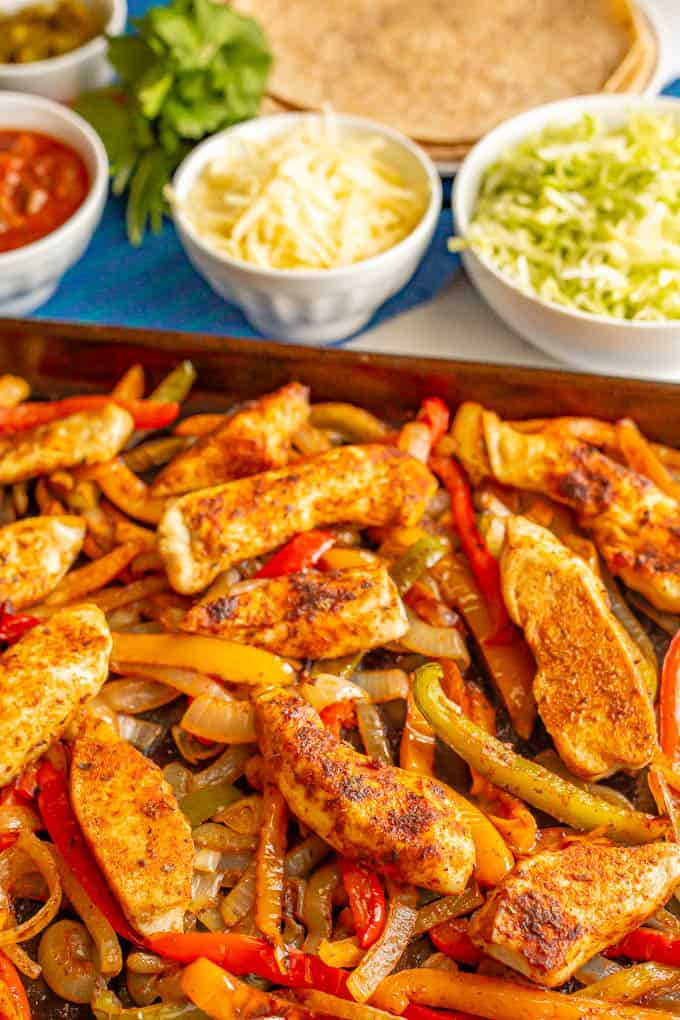 Roasted chicken fajitas with bell peppers and onions and nearby bowls of toppings