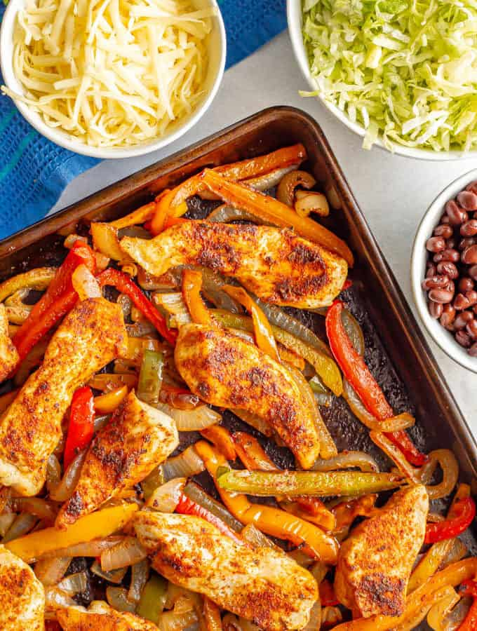 Roasted fajita chicken with bell peppers and onions and nearby bowls of toppings