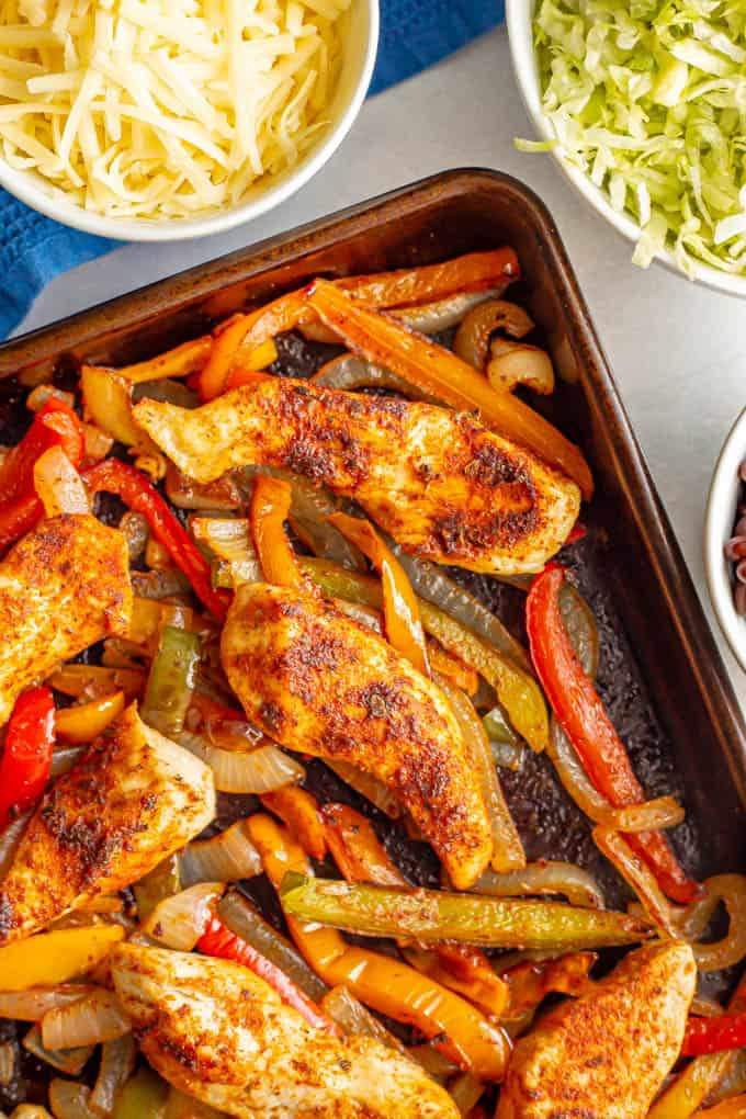 Sheet pan chicken fajitas with bell peppers and onions and nearby bowls of toppings