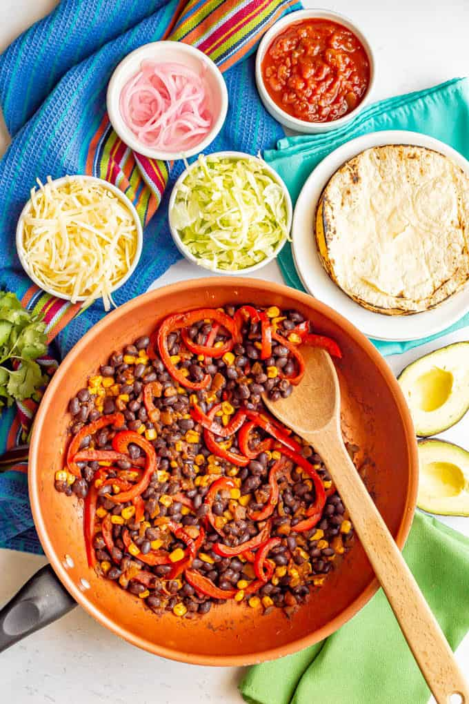 A skillet with black beans, peppers and corn surrounding by taco toppings in separate bowls