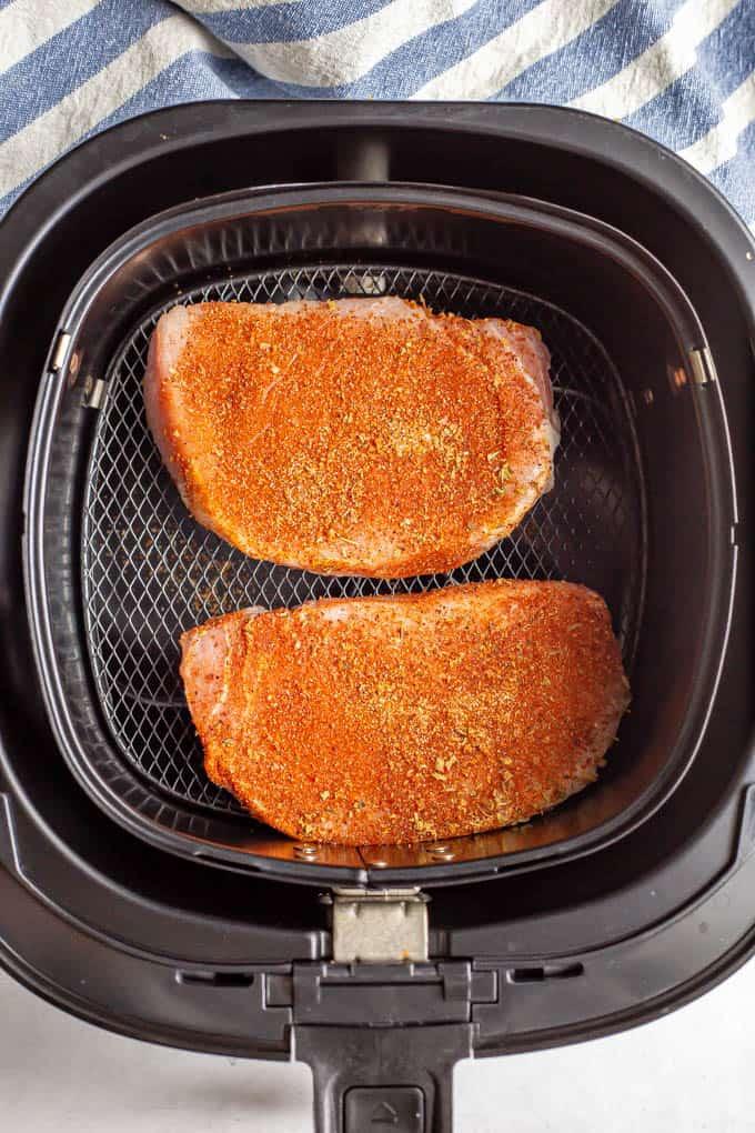 Seasoned pork chops in an Air Fryer before cooking